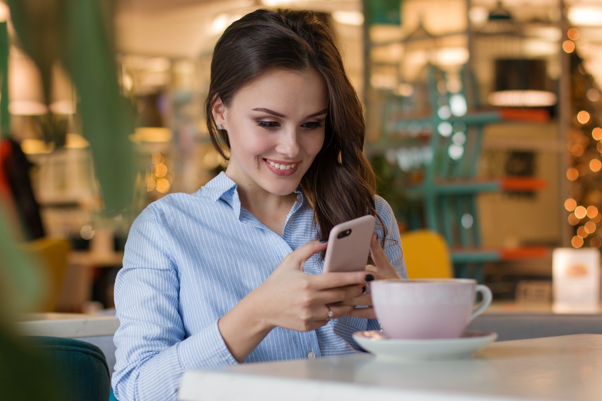 Happy woman with smartphone at restaurant