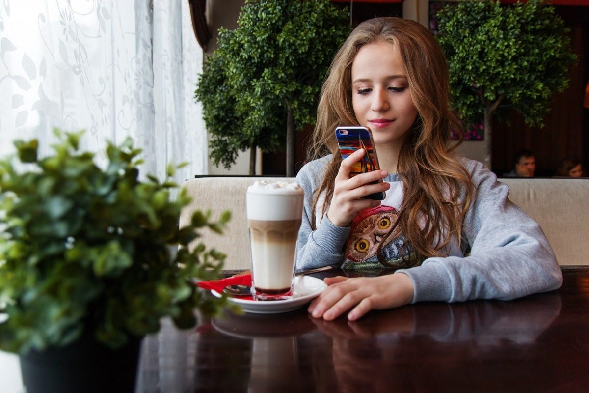 Girl with smartphone at coffee shop